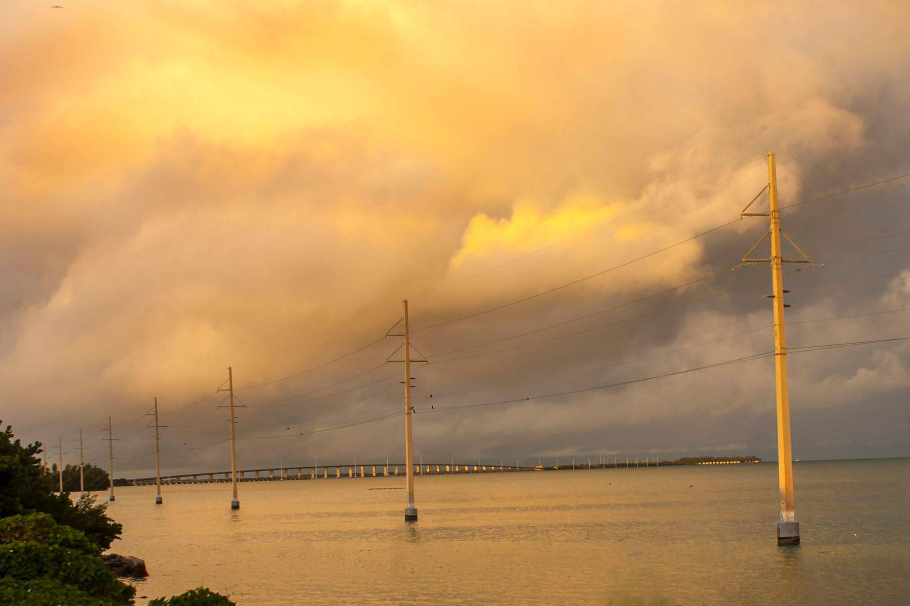 Transmission lines in florida keys duing sunrise, sea bridge